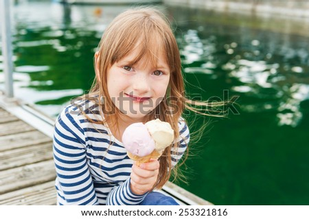 Outdoor portrait of a cute little girl, eating ice cream in a port - stock photo