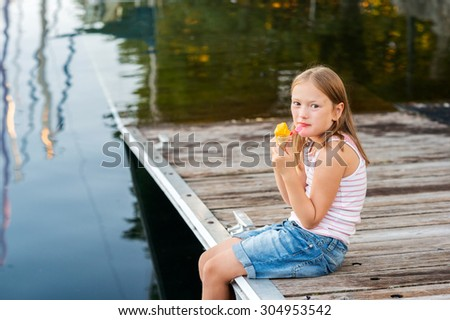 Outdoor portrait of a cute little girl, eating ice cream, resting by the lake - stock photo