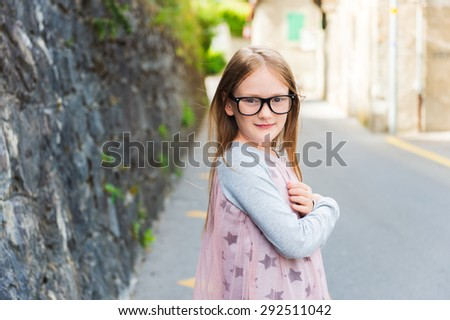 Outdoor portrait of a cute little girl in a city, wearing eyeglasses and dress - stock photo