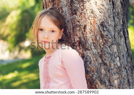 Outdoor portrait of a cute little girl of 7 years old, resting in a park, leaning on a tree