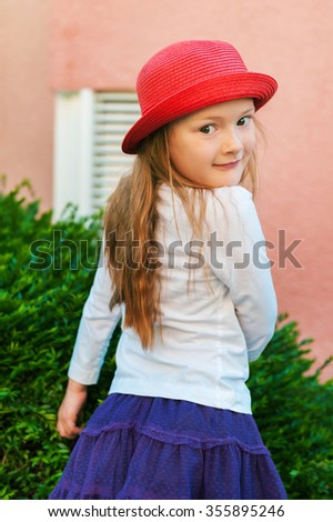 Outdoor portrait of a cute little girl of 5-6 years old wearing red hat - stock photo