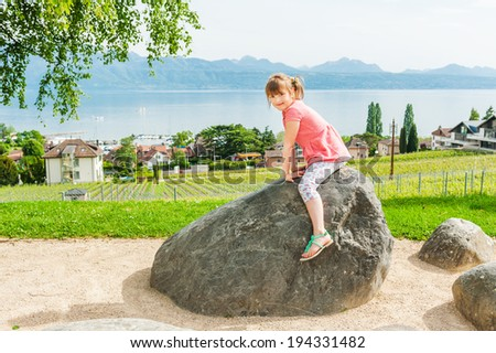 Outdoor portrait of a cute little girl on a nice sunny day, wearing coral dress and printed leggings