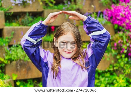 Outdoor portrait of a cute little girl under the rain, wearing purple rain coat, holding hands over the head - stock photo