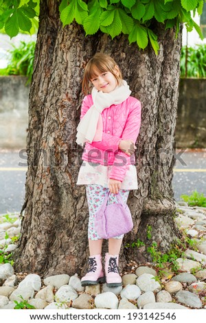 Outdoor portrait of a cute little girl; wearing pink jacket and boots, standing next to beautiful chestnut tree - stock photo