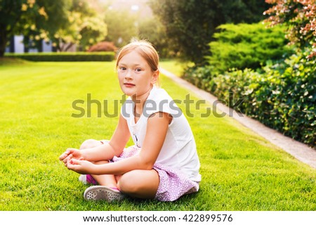 Outdoor portrait of a cute little kid girl of 7-8 years old, sitting on bright green lawn at sunset. Child playing on backyard in the evening - stock photo