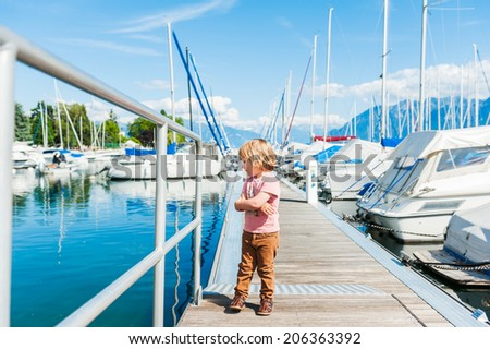 Outdoor portrait of a cute toddler boy in a port, on a nice sunny day