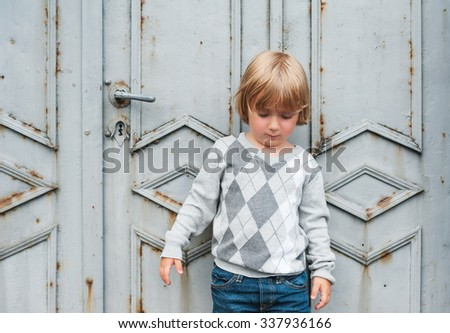 Outdoor portrait of a cute toddler boy wearing grey pullover - stock photo