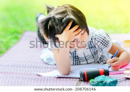 Outdoor portrait of a cute young Asian girl lying down on the mat and drawing. - stock photo