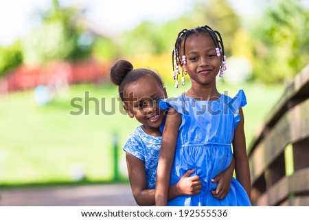 Outdoor  portrait of a cute young black sisters laughing - African people - stock photo