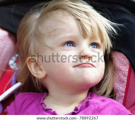 Outdoor portrait of a funny 2 years old baby girl - stock photo