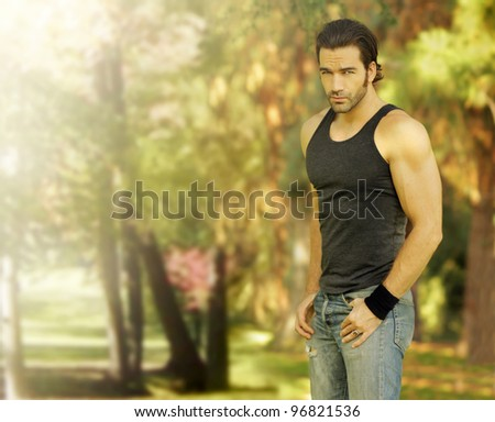 Outdoor portrait of a good looking male model in casual wear with beautiful natural background behind him - stock photo