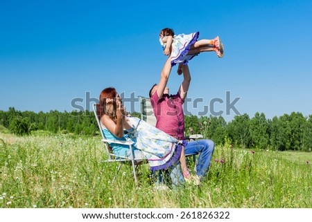 Outdoor portrait of a happy family. father picked up the child in her arms - stock photo