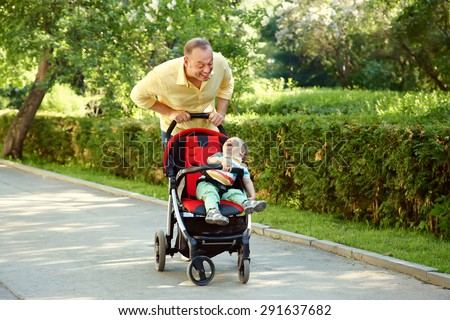 outdoor portrait of a happy father and son. baby sitting in stroller and dad walk in the summer park - stock photo