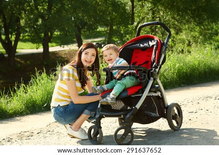 outdoor portrait of a happy mother and son. baby sitting in stroller and mom walk in the summer park - stock photo
