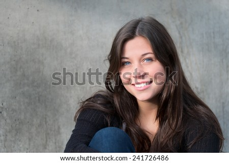 Outdoor portrait of a happy teenage girl smiling in front of a gray wall - stock photo