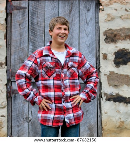 Outdoor portrait of a happy teenager smiling in front of an old barn door - stock photo