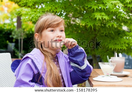 Outdoor portrait of a preschooler girl wearing rainy coat, sitting in cafe with ice cream and hot chocolate on a table