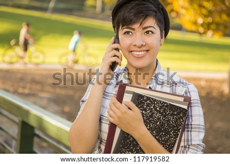 Outdoor Portrait of a Pretty Mixed Race Female Student Holding Books and Talking on Her Cell Phone on a Sunny Afternoon.