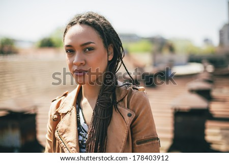 Outdoor portrait of a pretty young African woman. - stock photo