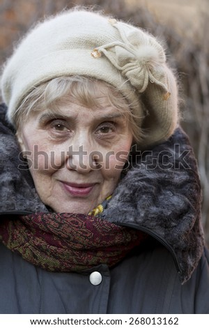 Outdoor portrait of a senior woman in jacket , scarf and head wear - stock photo