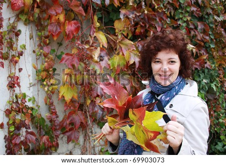 Outdoor portrait of a smiling senior woman  with red leaves in their hands.