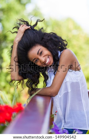 Outdoor portrait of a smiling teenage black girl - African people - stock photo
