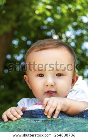Outdoor portrait of a sweet baby boy hiding behind a colored rock with a cheeky smile on his face, on a bright green background of leaves - stock photo