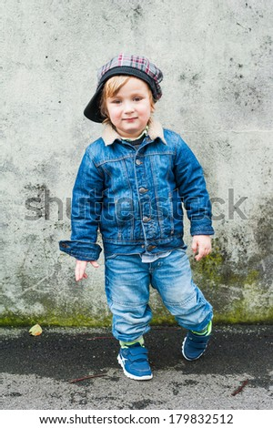 Outdoor portrait of a toddler boy, wearing jeans clothes - stock photo