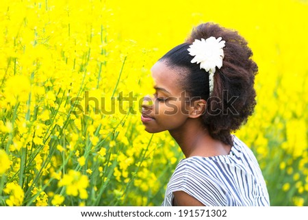 Outdoor portrait of a young beautiful african american woman in a rape colza field - Black people - stock photo