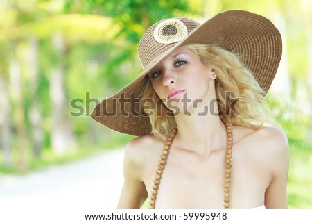 Outdoor portrait of a young beautiful woman in hat - stock photo