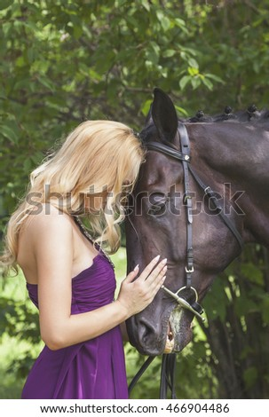 Outdoor portrait of a young blonde girl with long hair in a purple dress and a horse