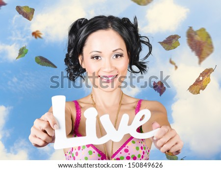 Outdoor portrait of a young girl holding out hands in joy and happiness to display the words live. Motivational words from a life coach - stock photo