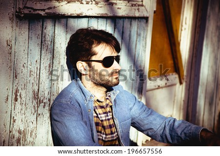 Outdoor portrait of a young stylish man in denim clothing  - stock photo