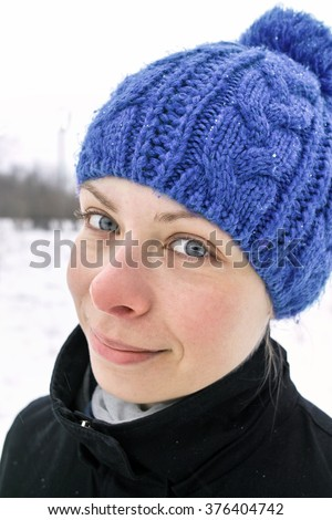 Outdoor portrait of a young woman with a light smile and ironic gaze - stock photo