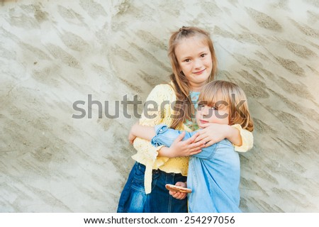Outdoor portrait of adorable kids hugging each other - stock photo