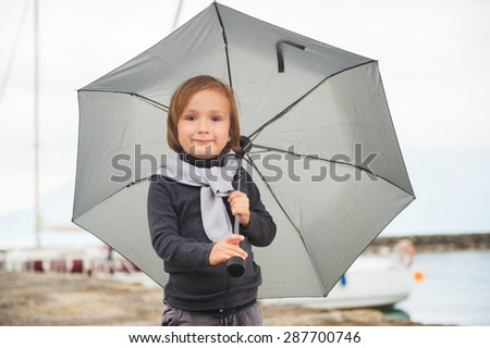 Outdoor portrait of adorable little boy with umbrella - stock photo