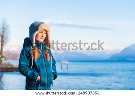 Outdoor portrait of adorable little girl on a nice winter evening, resting by the lake and watching the sunset - stock photo