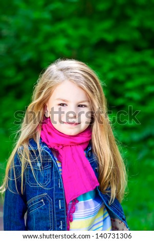 Outdoor portrait of an adorable smiling blond little girl wearing a blue jeans jacket and a pink scarf - stock photo