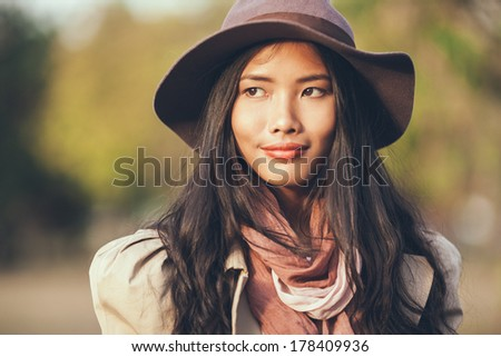 Outdoor portrait of an elegant smiling Asian woman.
