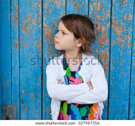 Outdoor portrait of angry little girl - stock photo