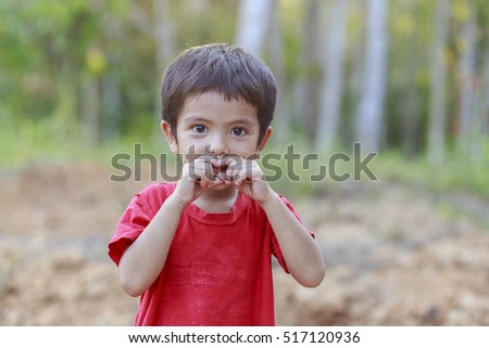 Outdoor portrait of Asian little boy covering his mouth with hand and looking at camera while standing