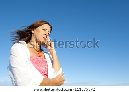 Outdoor portrait of attractive mature  woman looking depressed, worried, tired, isolated with blue sky as background and copy space. - stock photo