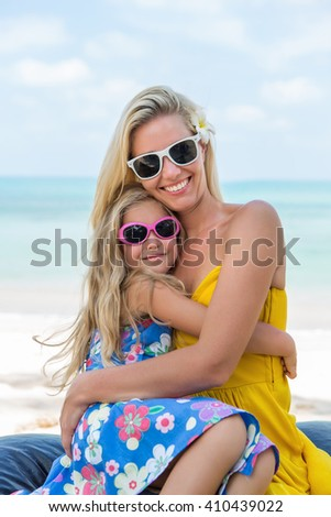 Outdoor portrait of beautiful blonde mother and her cute child. Small girl hugging her mammy on the beach. Little lady and mom wearing sunglasses. They smiling. Summer sunny day. Happy Mothers day.