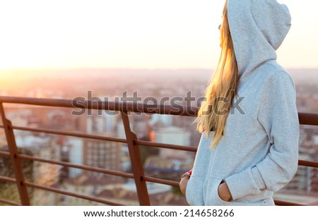Outdoor portrait of beautiful blonde stands on the edge of the roof. - stock photo