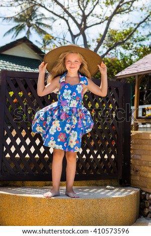 Outdoor portrait of beautiful girl in blue floral dress and beach straw hat. Beautiful lady touch her big hat and smile. Summer sunny day. House with wooden fence at tropical background. Mothers day. - stock photo
