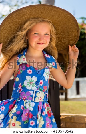 Outdoor portrait of beautiful girl in blue floral dress and beach straw hat. She holds her big hat and smile to camera. Summer sunny day. House with wooden fence at tropical background. Mothers day. - stock photo