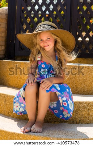 Outdoor portrait of beautiful girl in floral dress and beach straw hat. She sit on stairs and smile. Wind waves her blonde hair. Summer sunny day. Wooden fence at tropical background. Mothers day. - stock photo