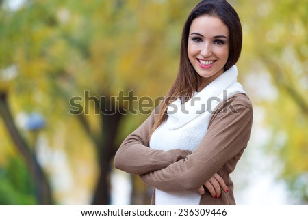 Outdoor portrait of beautiful girl looking at camera in autumn. - stock photo