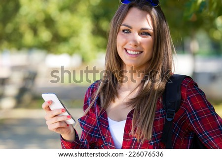 Outdoor portrait of beautiful girl using her mobile phone in city.