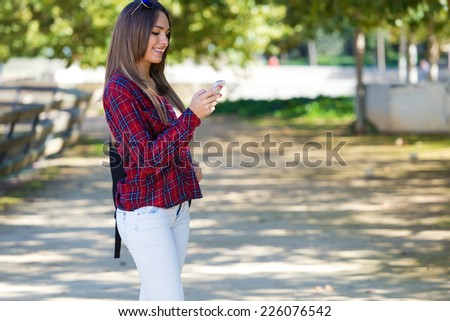 Outdoor portrait of beautiful girl using her mobile phone in city. - stock photo